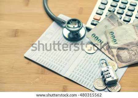 top view Stethoscope and combination padlock book bank calculator and money on wood floor with saving money plan for healthy