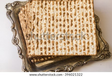 Top View to Jewish Matzoh on Decorated Silver Plate and White Background