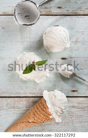 Top view vanilla ice cream in waffle cone with utensil on wood background. - stock photo