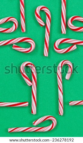 Top view vertical orientation shot of red and white stripped Christmas candy canes on a solid green background. Random patterns with canes in and out of the frame.