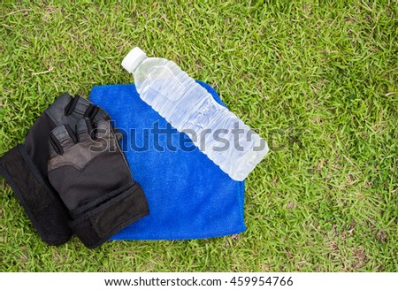 Top - view water bottle and towel with grass background.