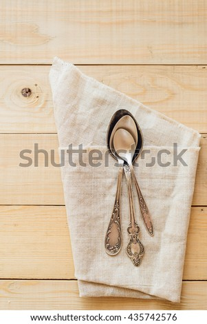 Top view wooden table setting with copyspace, three antique spoons on linen napkin - stock photo