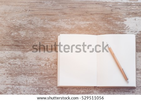 Top view work space notebook and brown pencil on wood table background,retro effect