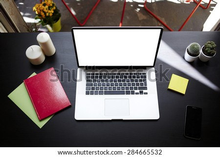 Top view Workplace with open computer, colorful notebooks and stickers,laptop with blank copy space empty screen for your content or text message,modern table at open window in home interior in summer - stock photo