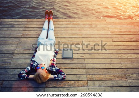 Top view young woman lying on a wooden jetty enjoying the sunshine,tourist girl in bright summer glasses lying on jetty by river, vintage photo of relaxing young woman in nature with tablet, flare sun - stock photo