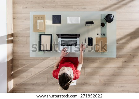 top view, young woman sitting at glass desk and working on her laptop, her table is perfectly tidy, the sun casts graphics shadows on the wood floor - stock photo