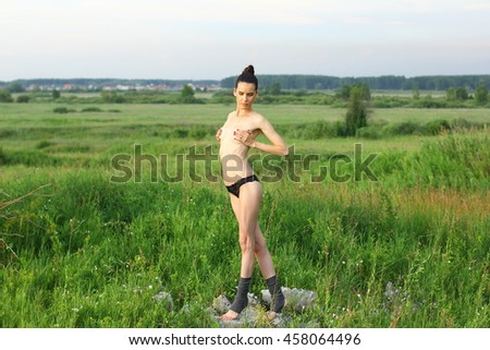 Topless beautiful ballerina dancing outdoors in a summer field. Ballerina Project. - stock photo