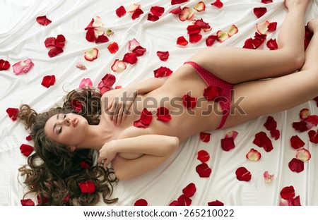 Topless girl posing in bed with rose petals - stock photo