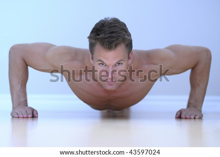 Topless male model performs pushup on floor. - stock photo