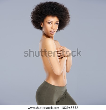 Topless provocative attractive young African American woman with a bushy afro hairstyle posing sideways concealing her breasts with her hands, square format on grey - stock photo