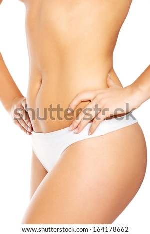 Topless woman touching her hips and showing her flat belly. Isolated on white.  - stock photo