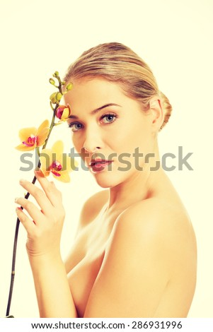Topless woman with an orange orchid flower. - stock photo
