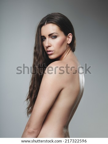 Topless young woman looking at you seductively against grey background. Naked female model with long brown hair.