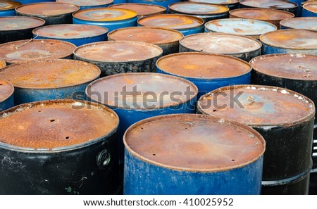 Tops of many rusted blue and black storage drums. - stock photo