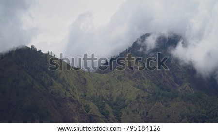Tops of the mountains covered with forest in clouds and fog. Slopes of the mountains are covered with rainforest Bali, Indonesia. Mountain landscape, sky and clouds. Travel concept