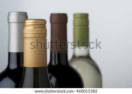 Tops of wine bottles showing different varietals - stock photo