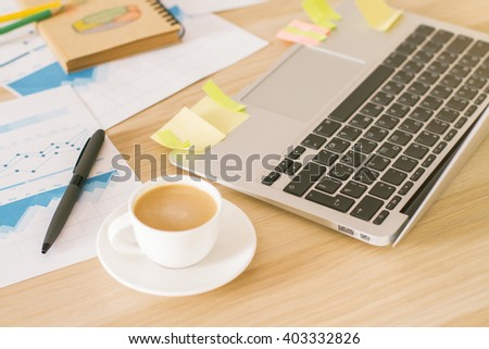 Topview of wooden desk with coffee cup, laptop keyboard and business charts - stock photo