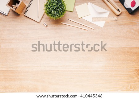 Topview of wooden desk with office tools and plant. Mock up - stock photo