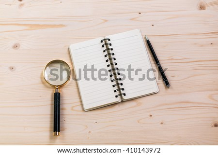 Topview of wooden desktop with open lined notepad, magnifier and pen - stock photo