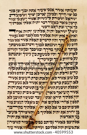 Torah scroll opened to Deuteronomy 6:4, known as the Shema, with a gold yad pointing to the place. - stock photo