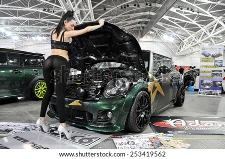 TORINO, ITALY - FEBRUARY 15, 2015: special version of cabriolet Mini Cooper S John Cooper Works tuned car with sensual and young model with high heels posing at Expo Tuning Torino on February 15, 2015 - stock photo