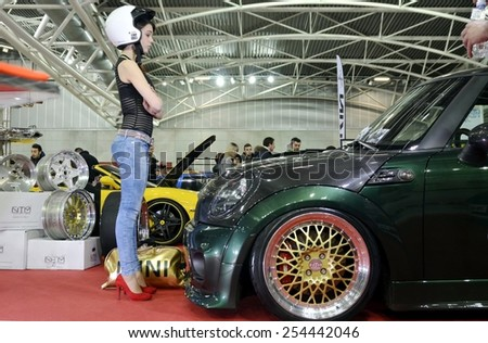 TORINO, ITALY - FEBRUARY 15, 2015: Young and sensual female pilot with helm posing in front of a Mini Cooper S John Cooper Works tuned car with gold wheels at Expo Tuning Torino on February 15, 2015 - stock photo