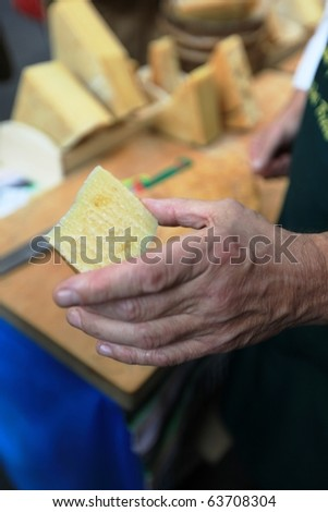 TORINO, ITALY - OCT. 24: Bitto cheese producer shows his product at Salone del Gusto, international fair of tastes and slow food October 24, 2010 in Torino, Italy. - stock photo