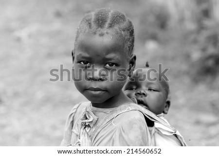TORIT, SOUTH SUDAN-FEBRUARY 21 2013: An unidentified little girl in charge of carrying her baby sister in Torit, South Sudan - stock photo
