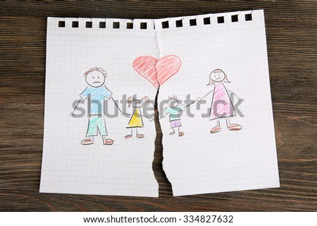 Torn apart drawing of a family on wooden background - stock photo
