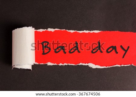 Torn black paper with red background and text Bad day - stock photo