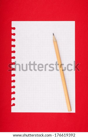 Torn blank lined notebook page with pencil on red background - stock photo