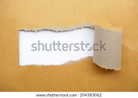 Torn brown envelope in the middle, showing white. - stock photo