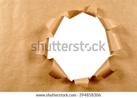 Torn brown paper background looking through hole, white copy space - stock photo