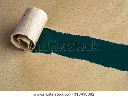Torn brown paper on blank green rough surface. - stock photo