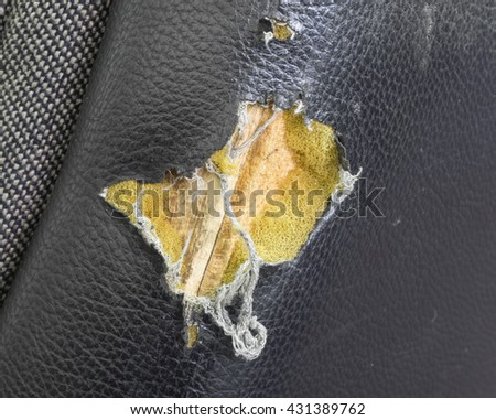 Torn leather at the back view of old black revolving office chair, selective focus - stock photo