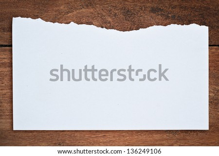 Torn paper on wood background - stock photo
