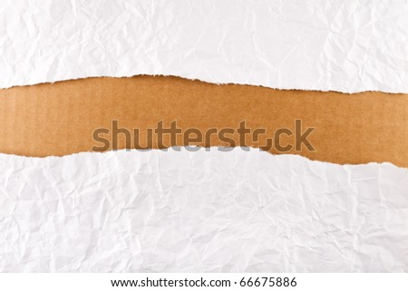 Torn paper-strip series - crumpled white paper revealing brown cardboard - stock photo