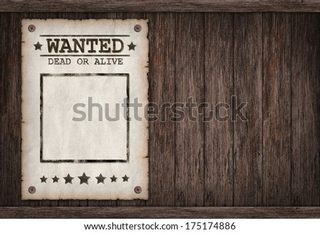 Torn Wild West wanted poster on old wooden wall  - stock photo