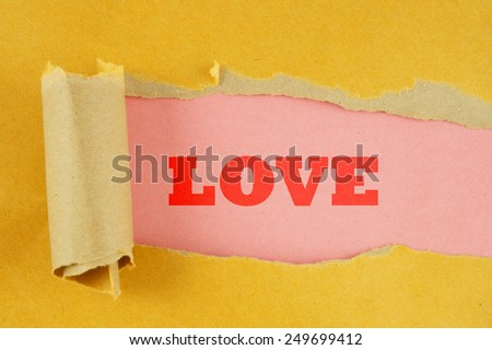Torn yellow paper with pink background and word love - stock photo