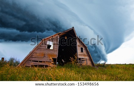 tornado forming behind old barn on american plains - stock photo