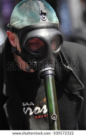 TORONTO - APRIL 20:  A masked marijuana smoker  smoking  from bong during the annual marijuana 420 event at Yonge & Dundas Square  on April 20  2012 in Toronto, Canada. - stock photo