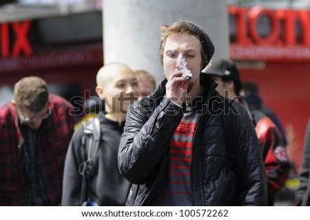 TORONTO - APRIL 20:  A young  adult smoking  marijuana during the annual marijuana 420 event at Yonge & Dundas Square  on April 20  2012 in Toronto, Canada. - stock photo