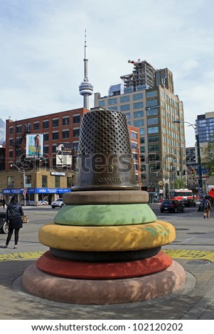 TORONTO - APRIL 22: Artist Stephen Cruise's ode to Toronto's fashion industry, a nine foot high stack of brightly colored buttons topped by a bronze thimble on April 22 2012, in Toronto, Canada. - stock photo