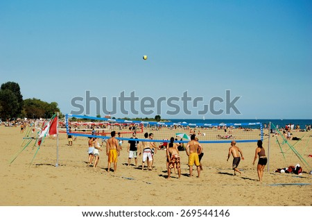 TORONTO - AUG 31: Young people playing beach volleyball on Woodbine Beach at Lake Ontario in east Toronto on August 31, 2008. - stock photo