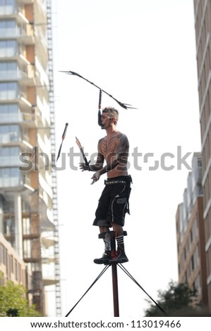 TORONTO-AUGUST 31: A  performer juggling with swords while high up in the air during the Buskerfest Festival on June 31, 2012 in Toronto, Canada. - stock photo
