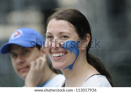 TORONTO-AUGUST 31:  A protester with painted dolphin on her cheek  during a rally to protest the start of the annual  dolphin hunt at Taiji,Japan on August  31, 2012 in Toronto, Canada. - stock photo