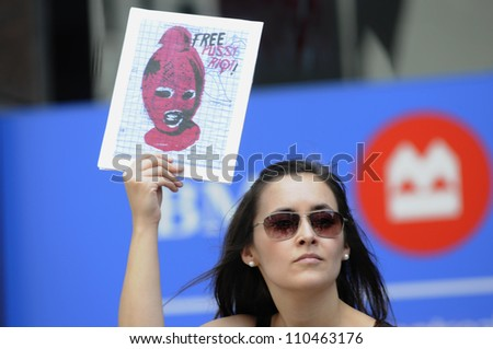 """TORONTO -AUGUST  17: A woman holds a placard  during a protest rally organized to free """"pussy riot""""on August 17 2012 in Toronto, Canada. - stock photo"""