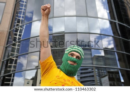 """TORONTO -AUGUST  17:  An angry protester underneath the building that holds the Russian Consulate during a protest rally organized to free """"pussy riot""""on August 17 2012 in Toronto, Canada. - stock photo"""