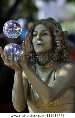 TORONTO-AUGUST 25: Dawns Dream a street performer performing  with a crystal ball during the Buskerfest Festival on August 25, 2012 in Toronto, Canada. - stock photo