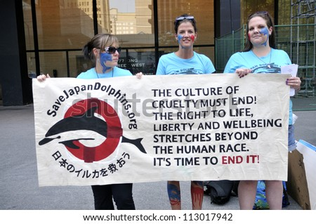 TORONTO-AUGUST 31: Protesters holding a sign to denounce the killing  of dolphins during a rally to protest the start of the annual dolphin hunt at Taiji,Japan on August 31,2012 in Toronto,Canada. - stock photo